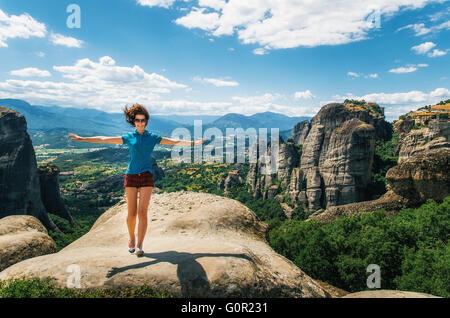 Glückliche junge Frau steht wieder auf den Felsen mit erhobenen Händen. Reisende genießen die Landschaft, Meteora, - Stockfoto