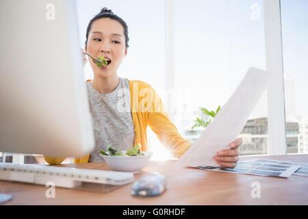 Eine schöne Geschäftsfrau, Essen und lesen - Stockfoto