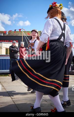 Drei Frauen in einem Morris tanzen Truppe zeigt fließende Kleider auf einem Yorkshire-Stein Pflaster mit Schaulustigen - Stockfoto