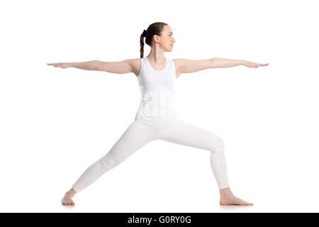 Sportlich schöne junge Frau in weißen Sportbekleidung Longe Übung, Warrior II Körperhaltung, Virabhadrasana 2, Höhenplan - Stockfoto