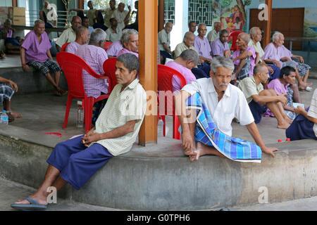 """Alte Männer sitzen im Hof der """"Prem Dan Heimstadion für Kranke und sterbende"""" Missionarinnen der Nächstenliebe (Mutter - Stockfoto"""