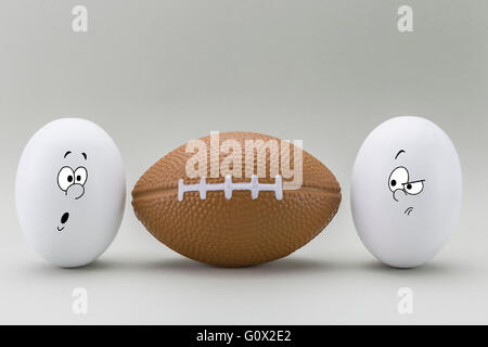 Zwei Eiern suchen mit seltsamen Gesicht an einem Ballon von rugby - Stockfoto