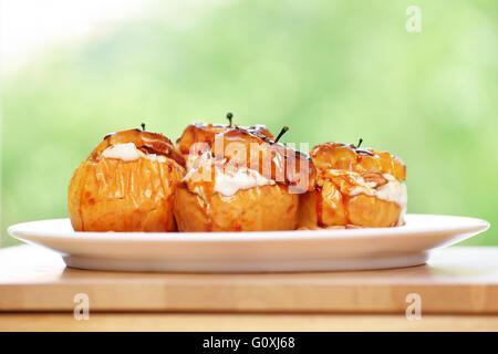 Nahaufnahme Foto von einem leckeren Bratäpfel gefüllt mit Käse Creme, gewürzt mit Zimt, Nüssen und Honig - Stockfoto