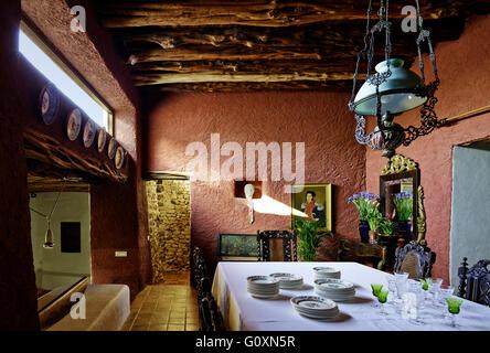 Landhaus Ibiza. Eine Villa Dining Raum mit roten Wänden.  Tisch mit Tuch und weiß China. - Stockfoto