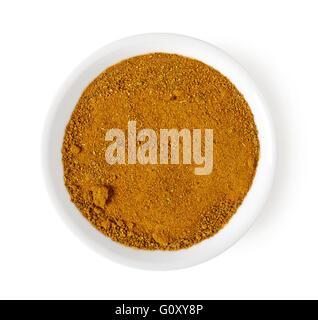 Schüssel mit Curry-Pulver isoliert auf weißem Hintergrund, Ansicht von oben - Stockfoto