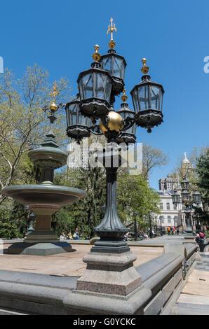 Blick auf kunstvolle Kandelaber und Wasser-Brunnen in City Hall Park, New York, mit dem Rathaus im Hintergrund. - Stockfoto