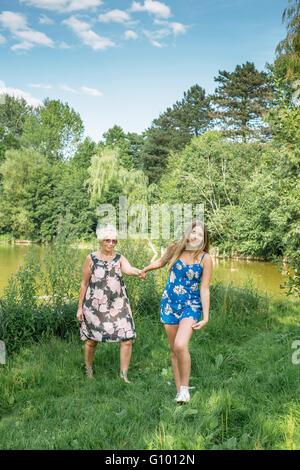 Mädchen zieht die Frau ihre Hand. Mutter und Tochter gehen. Großmutter und Enkelin. - Stockfoto