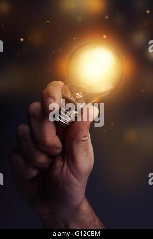 Kreative Energie und neuen Ideen, Hand Holding Glühbirne, getönten Retro Bild, selektiven Fokus. - Stockfoto
