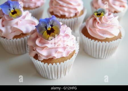 Hausgemachte rosa Zuckerguss Vanille Cupcakes mit essbaren Blüten - Stockfoto