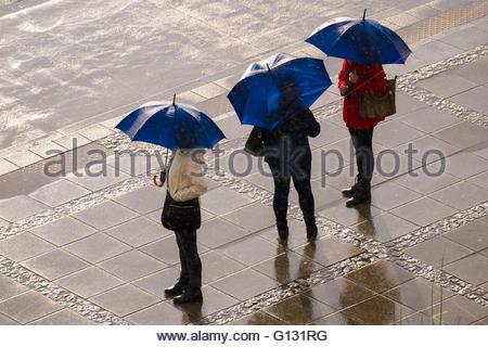 Drei Frauen mit gleichen blauen offenen Schirmen stehend auf einem Steinpflaster unter Regen und Sonne (von oben - Stockfoto