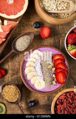 Acai Berry Smoothie Schüssel garniert mit Chia-Samen, Kokosflocken, Banane, Erdbeeren und Kiwi mit unterschiedlichsten - Stockfoto