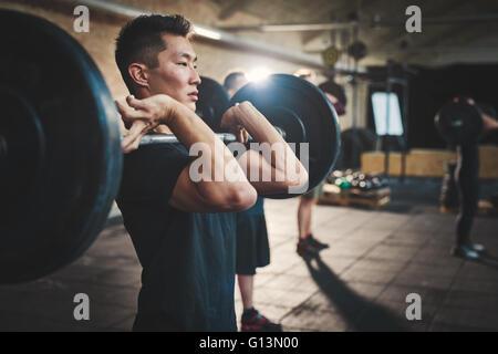Passen Sie jungen Mann Aufhebung Hanteln suchen konzentriert, trainieren Sie im Fitnessraum mit anderen Menschen - Stockfoto
