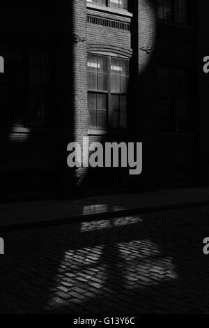 Sonnenstrahl trifft ein Backsteingebäude in einer DUMBO-Straße in Brooklyn. Monochrom, schwarz / weiß - Stockfoto