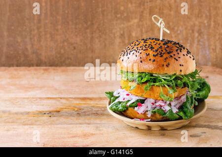 Hausgemachte vegetarische Süßkartoffel-Burger mit frischen Radieschen und Erbsen-Sprossen auf Ton Platte über hölzerne - Stockfoto