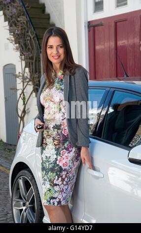 Schöne junge Frau (Alter 20-30) von ihrem Auto, hält die Schlüssel - Stockfoto
