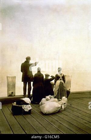 """Unter dem Titel: """"vier Einwanderer und ihre Habseligkeiten, auf einem Dock, Blick auf das Wasser; Ansicht von hinten. - Stockfoto"""