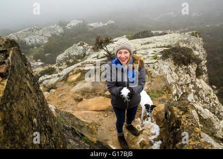 Porträt von weiblichen Wanderer mit ihrem Hund hält Schneeball in nebligen Bergen, Spanien - Stockfoto