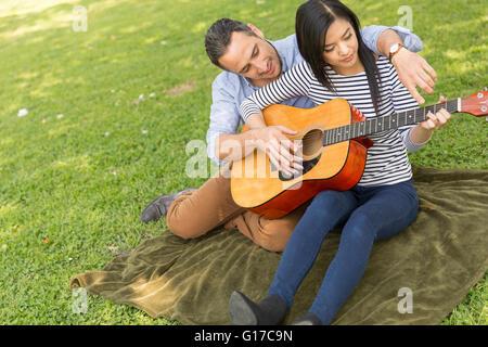 Mann sitzt auf dem Rasen unterrichten Frau, akustische Gitarre zu spielen - Stockfoto