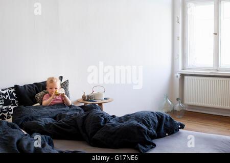 Baby Mädchen, sitzen im Bett, trinken aus Baby-Flasche - Stockfoto