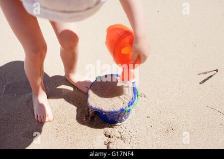 Babymädchen gießt Wasser auf Eimer mit Sand, erhöhte Ansicht - Stockfoto