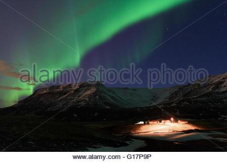 Aurora Borealis über Schnee bedeckt Berge, Hrafnaholar, Island - Stockfoto