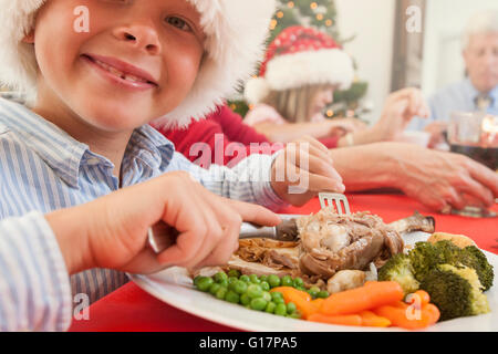 Jungen tragen Nikolausmütze Weihnachten Essen Blick auf die Kamera zu Lächeln - Stockfoto