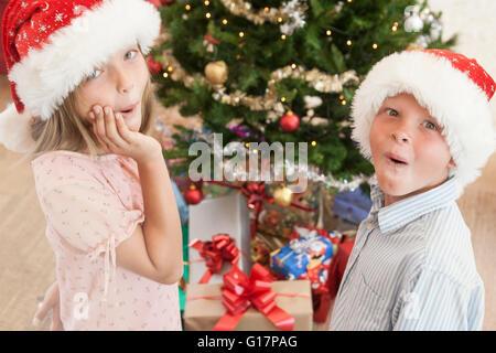 Mädchen und jungen in Santa hüten vor Weihnachtsbaum Blick in die Kamera aufgeregt - Stockfoto