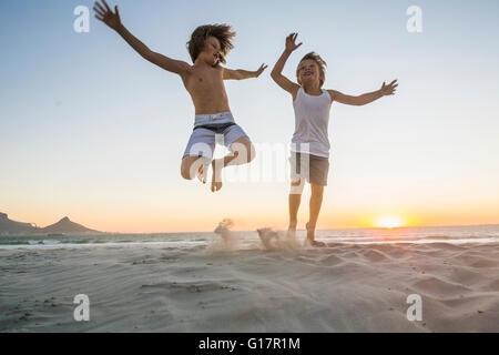 Brüder am Strand bei Sonnenuntergang in der Luft springen - Stockfoto