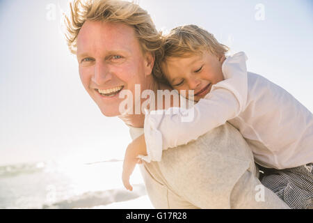 Vater am Strand geben Sohn Huckepack Blick auf die Kamera zu Lächeln - Stockfoto