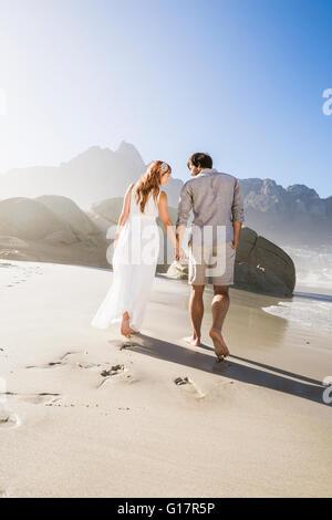 Voller Länge Rückansicht des Paares zu Fuß am Strand Hand in Hand - Stockfoto