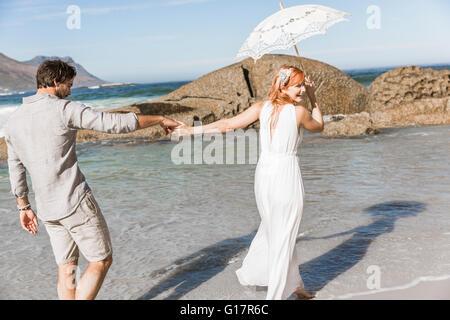 Paar Hand in Hand, zu Fuß auf Küste hält Regenschirm mit Blick auf die Schulter lächelnd - Stockfoto