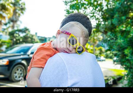 Vater mit schlafenden Jungen gelbe Sonnenbrille - Stockfoto