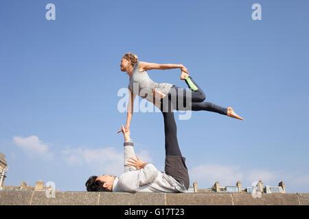 Mann und Frau üben akrobatische Yoga an Wand - Stockfoto