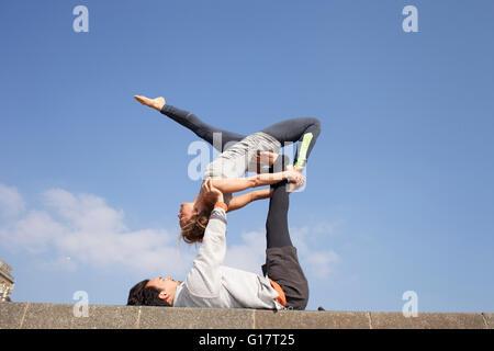 Mann und Frau an Wand akrobatische Yoga zu praktizieren - Stockfoto