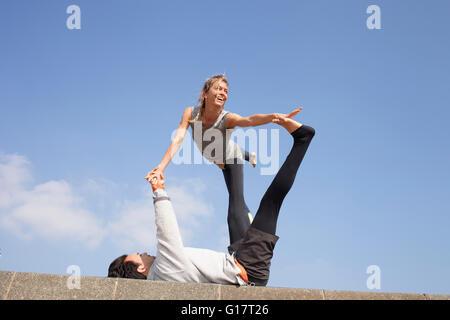 Mann und Frau an Wand akrobatische Yoga zu praktizieren
