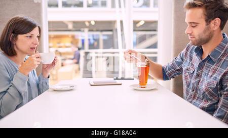 Frau zieht ihr Gesicht lustig, wie sie bei ihren männlichen Partner sieht, während er seine Teebeutel aus seinen - Stockfoto