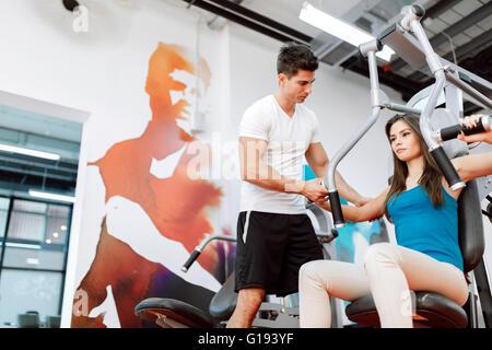 Schöne Frau, Turnen in der Turnhalle mit etwas Hilfe von personal trainer - Stockfoto