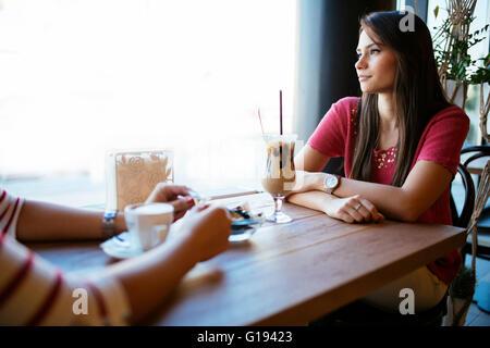 Schöne Frau im Gespräch mit Freund im Restaurant beim Kaffeetrinken - Stockfoto