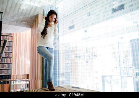 Geschäftsfrau mit Handy drinnen und lächelnd - Stockfoto