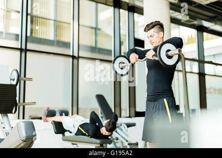 Hübscher Jüngling Training in einem Fitnesscenter - Stockfoto