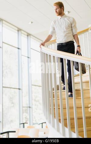 Gut aussehend Geschäftsmann zu Fuß die Treppe hinunter, während eine Tasche halten - Stockfoto