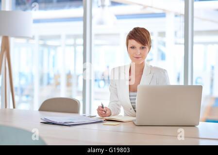 Porträt von eine junge Geschäftsfrau mit einer modernen Frisur und Anzug, bequem lächelnd in die Kamera während - Stockfoto