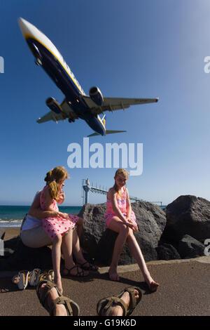 Leute sitzen in der Nähe von einem Strand auf Lanzarote, unterhalb einer Flugbahn RyanAir Flugzeug fliegen enge - Stockfoto