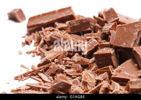 Stapel gebrochen und rasierte Schokoladenstücke, Isolated on White Background. - Stockfoto