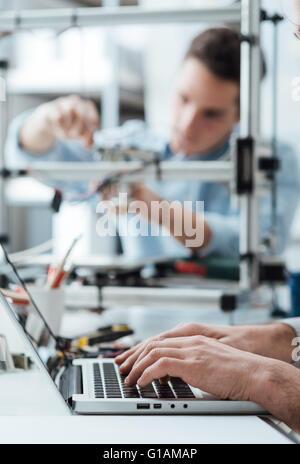 Ein Student ist ein 3D-Drucker Komponenten anpassen, derjenige im Vordergrund ist mit Engineering-Studenten arbeiten - Stockfoto