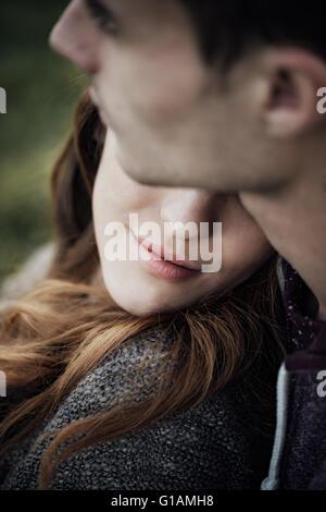Junge liebende Paar entspannen auf dem Rasen und umarmt, sie lächelt und stützte sich auf seine Schulter, Beziehungen - Stockfoto