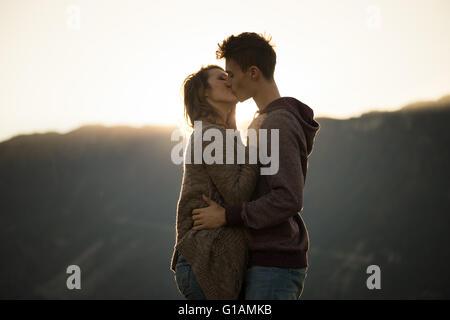 Romantische junge Paar küssen leidenschaftlich bei Sonnenuntergang, Berge im Hintergrund, Gefühle und Beziehungen - Stockfoto