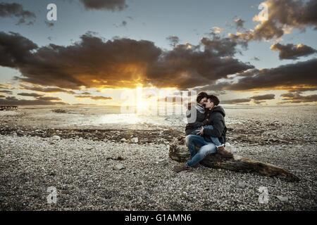 Junges Paar mit einem romantischen Date am See, sie umarmen und sitzen auf einem Baumstamm auf dem Strand, Liebe - Stockfoto