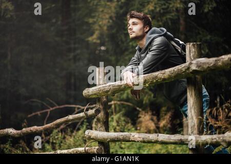 Junger Mann mit Rucksack wandern im Wald und stützte sich auf einen Holzzaun, Natur und Sport-Konzept - Stockfoto