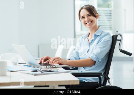 Sicher glücklich Geschäftsfrau im Rollstuhl am Schreibtisch arbeiten und einen Laptop verwenden, sie lächelt in - Stockfoto